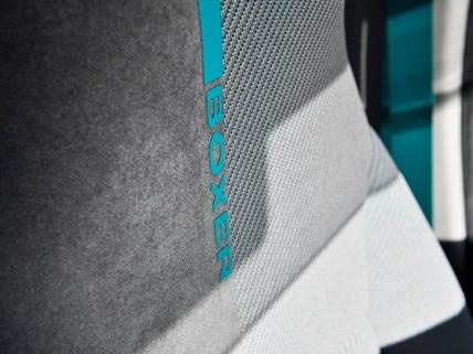 PEUGEOT BOXER 4x4 CONCEPT : . La deportiva malla técnica se combina con un Alcantara® GRIS GREVAL tomado de las nuevas tapicerías de los PEUGEOT e-208 GT, 508 HYBRID GT, 508 SW HYBRID GT y 3008 HYBRID4.